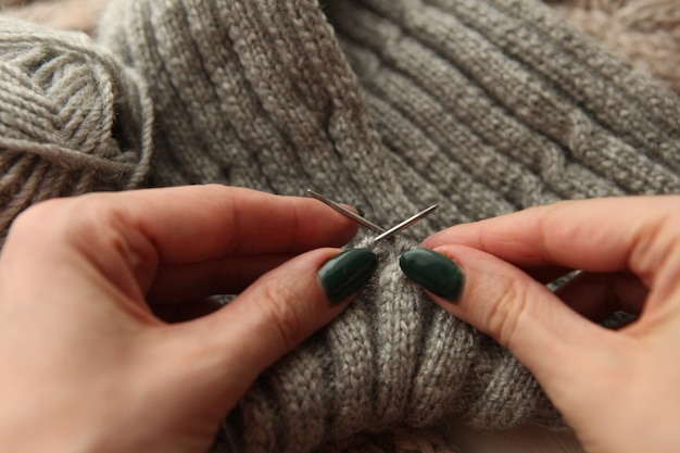 Lavoro a maglia - le mani della giovane donna che utilizzano ferri da maglia e rotolo di lana grigia. sciarpa lavorata a maglia con le mani della donna