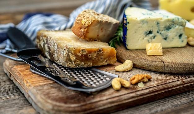 Coltelli e vari formaggi sul piatto di legno