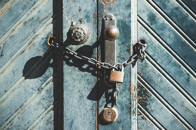 Manopola e lucchetto su una porta di legno blu stagionata di una vecchia fabbrica