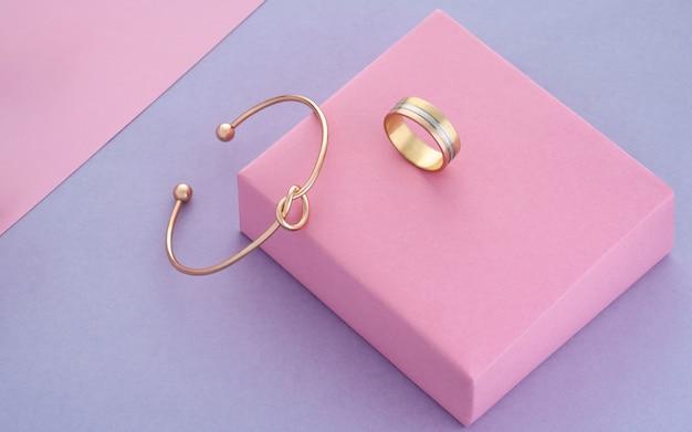 Bracciale e anello dorati a forma di nodo su sfondo di carta rosa e viola con spazio per le copie