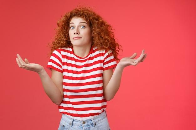 Non so chiedere a qualcun altro. inconsapevole inconsapevole carina rossa dai capelli ricci affascinante ragazza moderna incerta dove trascorrere le vacanze estive alzando le mani allargate lateralmente sogghignando confuso sfondo rosso.