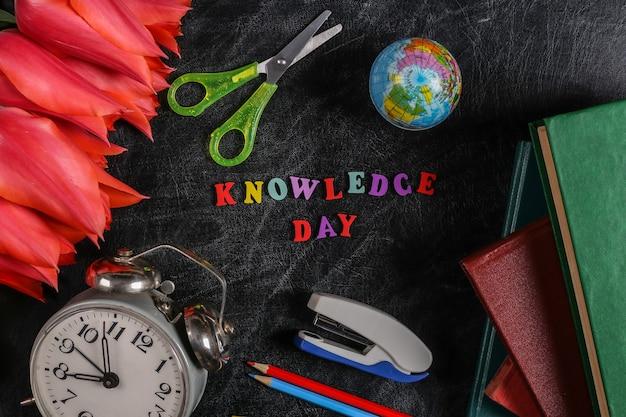 Giornata della conoscenza. tulipani rossi, materiale scolastico sulla lavagna. vista dall'alto. di nuovo a scuola