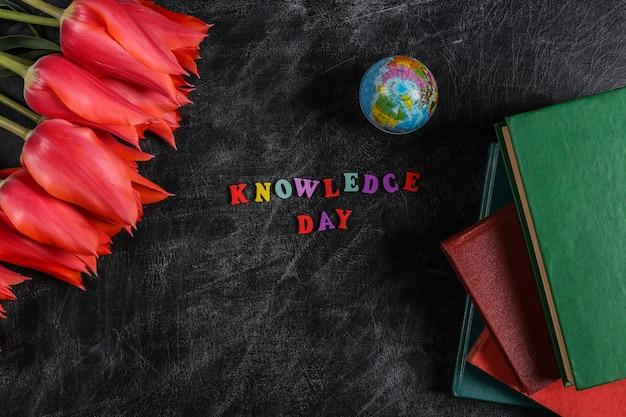 Giornata della conoscenza. tulipani rossi, pila di libri, globo sulla lavagna. vista dall'alto. di nuovo a scuola