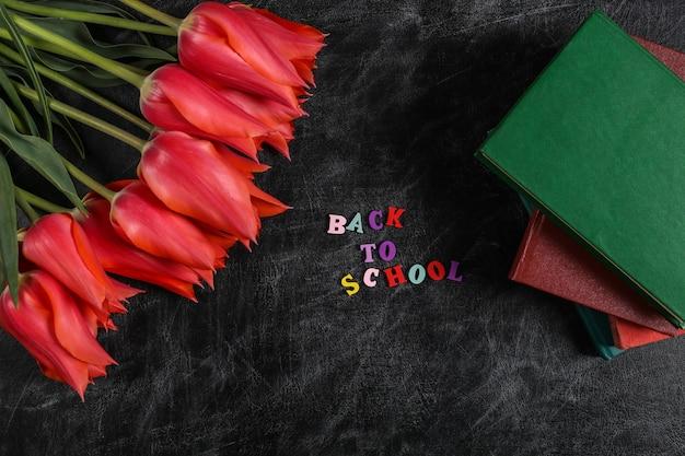 Giornata della conoscenza. tulipani rossi con pila di libri sulla lavagna. vista dall'alto. parola di ritorno a scuola