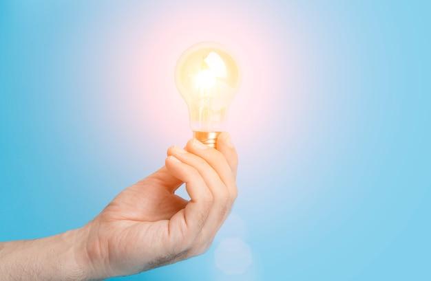 Conoscenza e concetto di idea lampadina con luce in mano su uno sfondo blu vuoto saggezza del cervello kno...