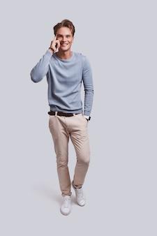 Sapere è potere. integrale di bel giovane che punta alla testa con il dito e sorride mentre si trova in piedi su sfondo grigio gray