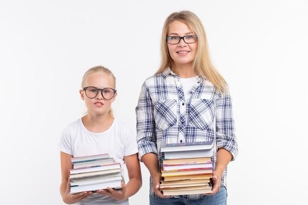 Conoscenza, lettura e concetto di educazione - madre e figlia che tengono un libro sul muro bianco.