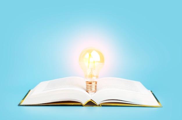 Concetto di apprendimento dello studio della conoscenza libro aperto con una lampadina incandescente su uno sfondo blu ricerca r...