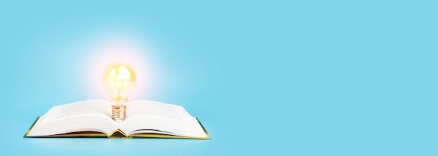 Concetto di apprendimento dello studio della conoscenza libro aperto con una lampadina incandescente su uno sfondo di banner blu res...