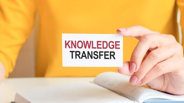 Il trasferimento delle conoscenze è scritto su un biglietto da visita bianco. la mano di una donna tiene una carta di carta bianca.