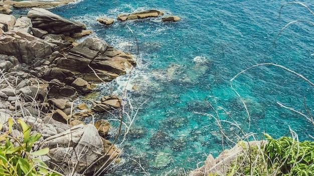 Isole di koh tao in thailandia. acqua blu chiara che colpisce le rocce.