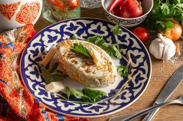 Kok-samsa con erbe e formaggio. focaccia di pasta sottile con ripieno di formaggio suluguni ed erbe aromatiche su un piatto con un motivo tradizionale uzbeko