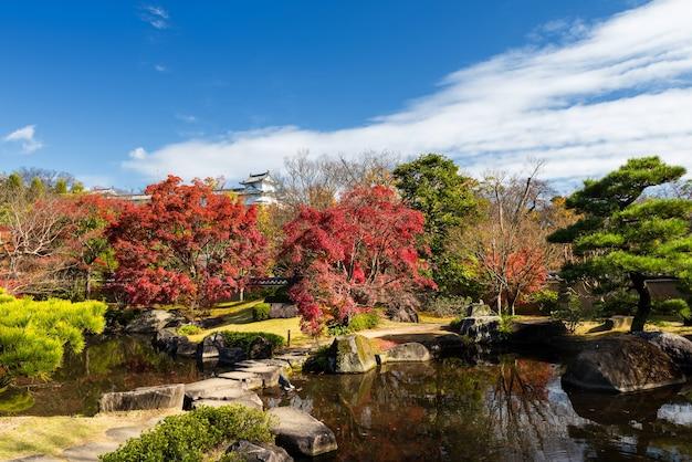 Koko-en autunno giardino e stagno con riflesso sullo skyline e castello di himeji a hyogo, giappone,