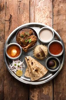 Il pollo kolhapuri thali è un popolare piatto indiano e asiatico composto da carne di pollame, uova al curry con chapati, riso, insalata e dolce gulab jamun