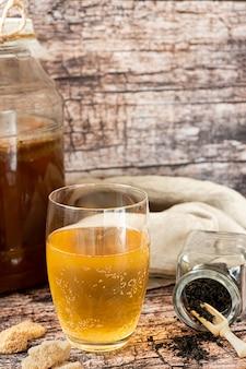 Kombucha fermentato bevanda salutare servita in un bicchiere su un tavolo rustico con ingredienti