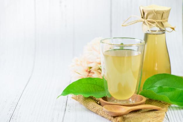 Tè kombucha con tiliacora triandra o foglia di erba di bambù, bevanda fermentata con sidro. i benefici del tè kombucha sono fonte di probiotici, ricchi di antiossidanti e contengono vitamine e minerali.