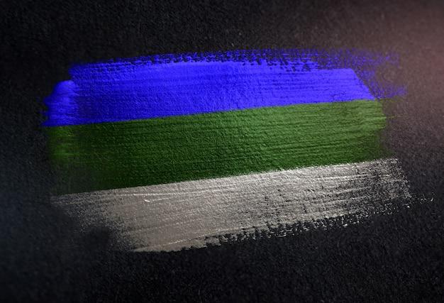 Bandiera della repubblica di komi fatta di vernice spazzola metallica sulla parete scura del grunge
