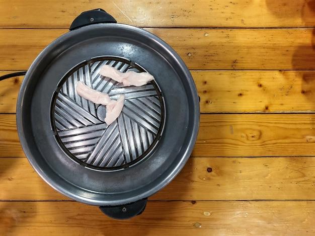 Barbecue coreano in cibo in stile tailandese: vista dall'alto della padella elettrica nera con lardo di maiale messo su un tavolo di legno