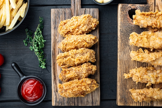 Tagli di pollo fritto barbecue coreano sul tavolo di legno nero, piatto laici