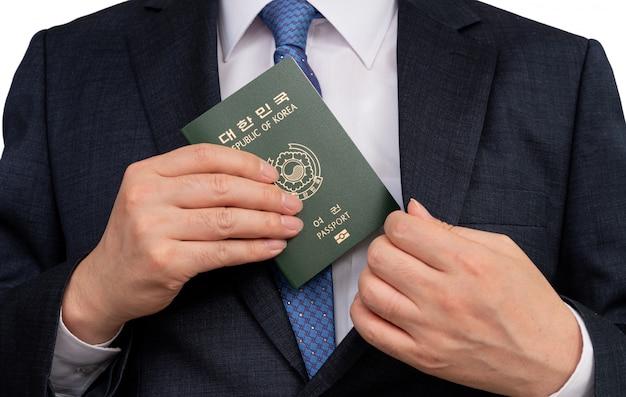 Uomo d'affari coreano che tiene in mano un passaporto coreano.