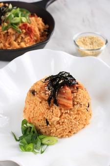 Cibo coreano: bokkeumbap o riso fritto con kimchi, riso fritto con ricetta tradizionale della corea del sud con kimchi, cipollotto, semi di sesamo, pomodoro e nori (laver)