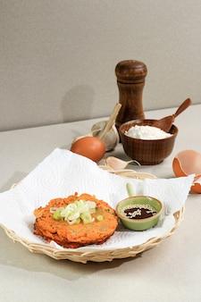 Cibo coreano: pancake coreano kimchi jeon. uovo in padella, kimchi e farina. servito su piatto in rattan con copia spazio per il testo