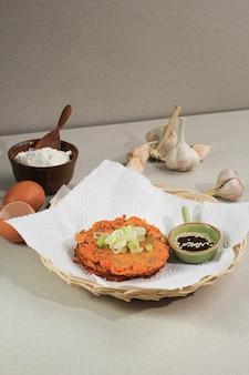 Cibo coreano: pancake coreano kimchi jeon. uovo in padella, kimchi e farina. servito con salsa di soia su piastra in rattan con copia spazio per il testo