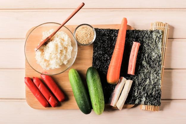 Coreano roll gimbap (kimbob o kimbap) preparazione degli ingredienti. riso, salsiccia, polpa di granchio, alga marina, cetriolo, carota e semi di sesamo