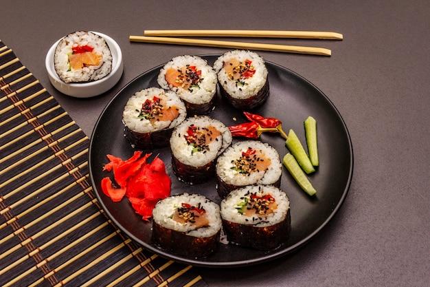 Rotolo coreano gimbap (kimbob). riso bianco al vapore (bap) e vari altri ingredienti. sfondo nero alla moda
