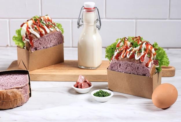 Pane viola panino coreano (goccia d'uovo) con uovo sodo, lattuga, maionese, salsa di pomodoro. copia spazio per testo o pubblicità