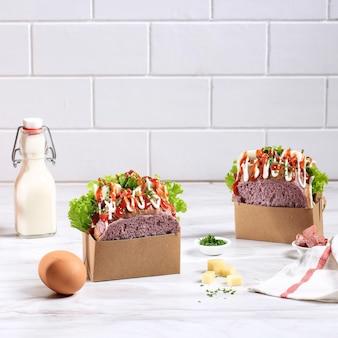 Pane viola panino coreano (goccia di uova) con uovo, lattuga, maionese, formaggio, prezzemolo, salsa. servito con latte. concetto di sfondo bianco per panetteria o pubblicità