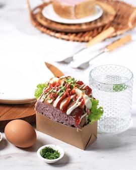 Panino coreano pane viola goccia d'uovo con lattuga salsa maionese servita con acqua fresca