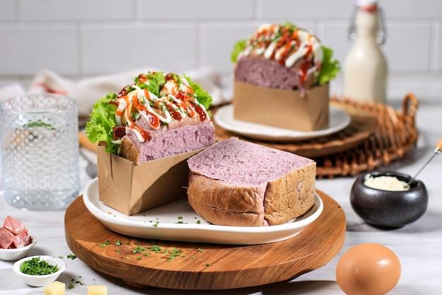 Pane viola panino coreano (goccia di uova) con uovo, lattuga, maionese, salsa. servito con latte. jiwa toast fatto in casa