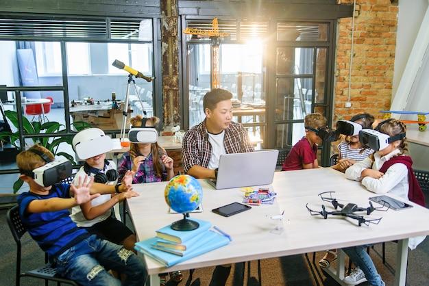 Insegnante coreana con sei allievi caucasici che usano gli occhiali vr di realtà aumentata in un'aula elementare di informatica