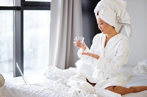 Donna coreana che prende una pillola, seduta sul suo letto a casa, indossando accappatoio e asciugamano, tenendo in mano farmaci o vitamine e un bicchiere d'acqua
