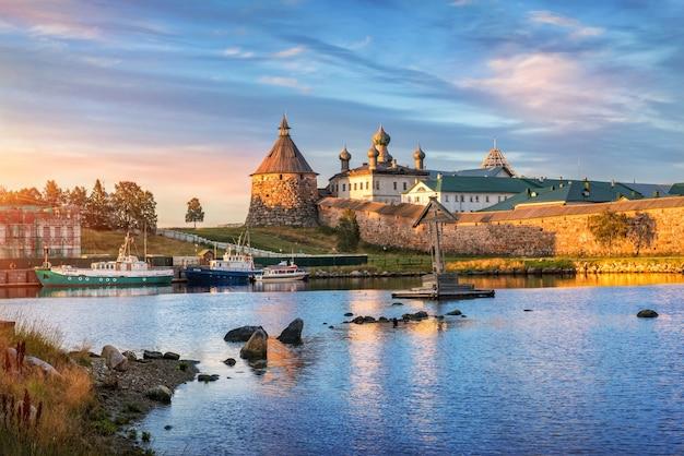 La torre korozhnaya del monastero di solovetsky sulle isole solovetsky e le navi nella baia della prosperità sotto i raggi del sole al tramonto. iscrizioni: san nicola. pechak.