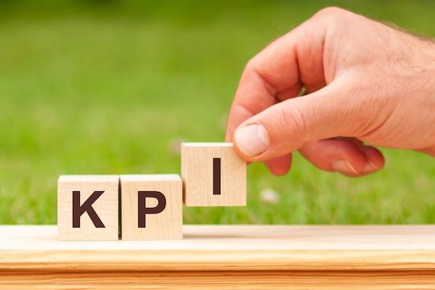 Kpi è una parola scritta su blocchi di legno. la mano di un uomo tiene un cubo di legno con la lettera i dalla parola kpi