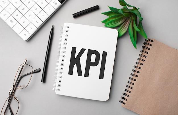 Kpi è scritto in un quaderno bianco con calcolatrice, blocco note colorato, pianta, pennarello nero e occhiali