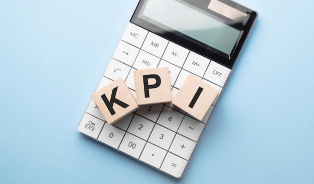 Kpi, indicatore di prestazioni chiave per il concetto di obiettivo aziendale, blocchi cubici che costruiscono la parola acronimo e calcolatrice