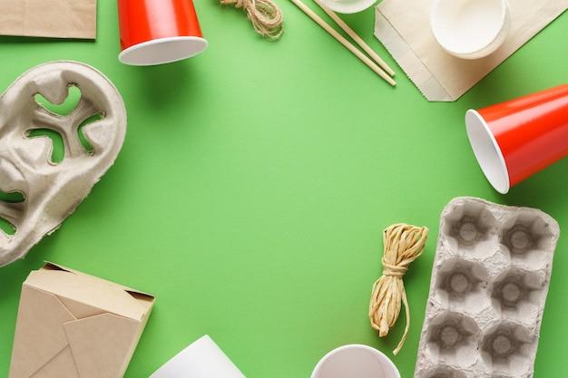 Carta kraft imballaggi alimentari ecologici e stoviglie su sfondo verde. zero rifiuti e concetto di riciclaggio. copia spazio.