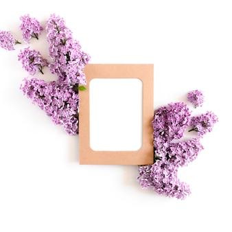 Cornice di carta kraft mock up, fiori lilla su uno sfondo bianco