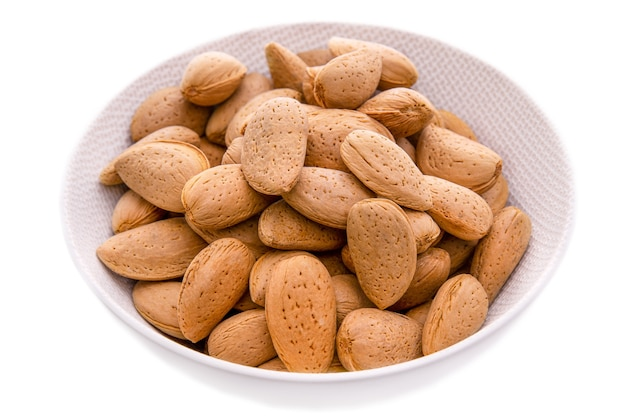 Krahmandelnun semi di mandorle pelati in un piatto bianco su uno sfondo bianco oggetti e prodotti isolati