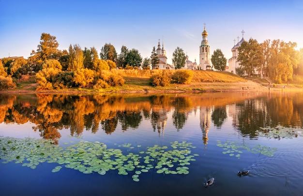 Templi del cremlino e ninfee e anatre nel fiume a vologda alla luce di una sera d'estate