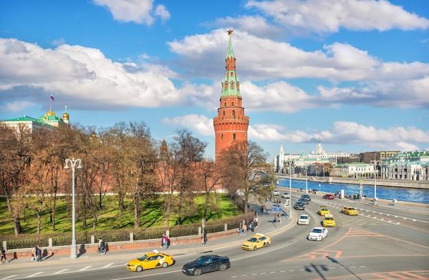 Torre del cremlino e auto taxi sull'argine a mosca in una giornata di sole estivo