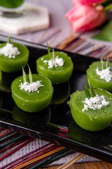 Kue lumpang pandan o kue ijo kue ijo è una torta verde tradizionale ed è di piccole dimensioni cotta a vapore e ha una consistenza gommosa servita con cocco grattugiato il suo spuntino popolare dall'indonesia