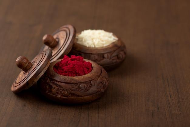 Kumkum e contenitore per chicchi di riso. le polveri di colore naturale vengono utilizzate mentre si adora dio e in occasioni di buon auspicio.