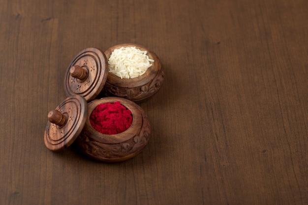 Kumkum e contenitore del chicco di riso su fondo di legno.