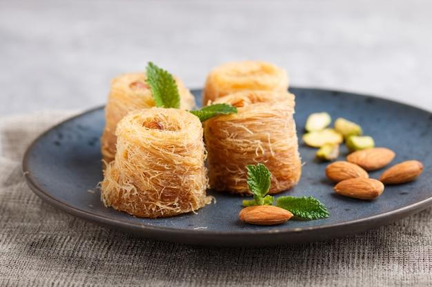 Kunafa, dolci arabi tradizionali nella fine ceramica blu del piatto su.
