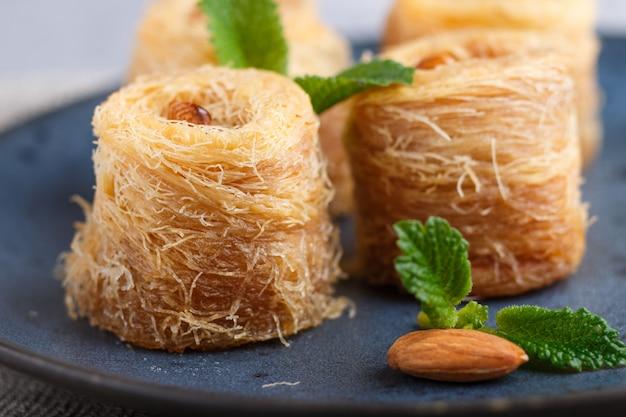 Kunafa, dolci tradizionali arabi nel piatto in ceramica blu su uno sfondo grigio cemento.