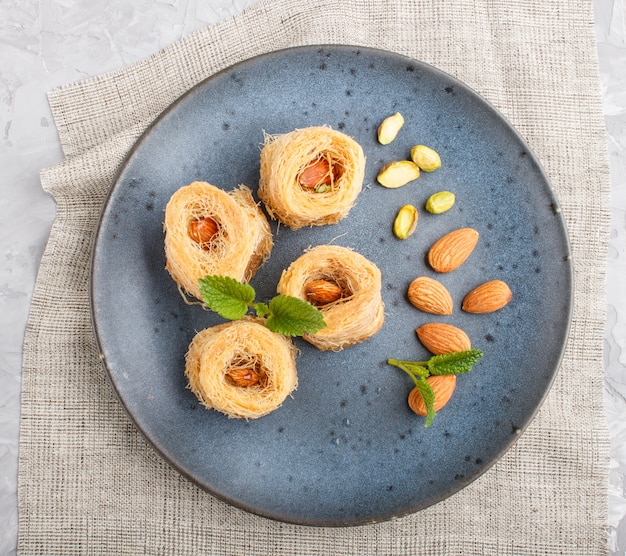 Kunafa, dolci tradizionali arabi nel piatto di ceramica blu su un cemento grigio. vista dall'alto.